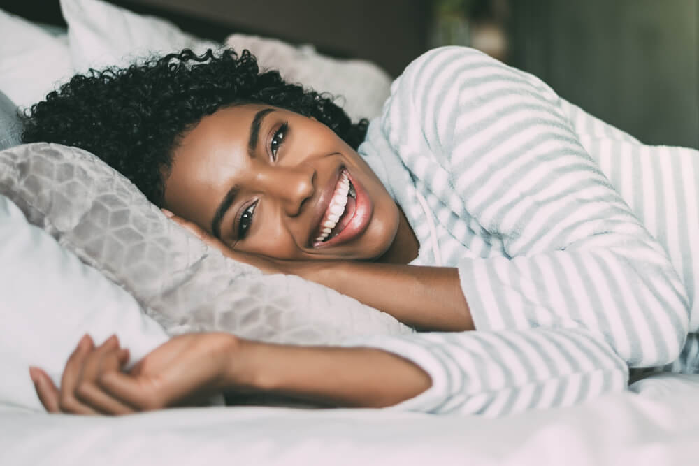 smiling woman laying in comfortable bed