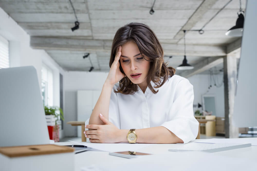 brunette woman sitting at desk with hand to her head in pain