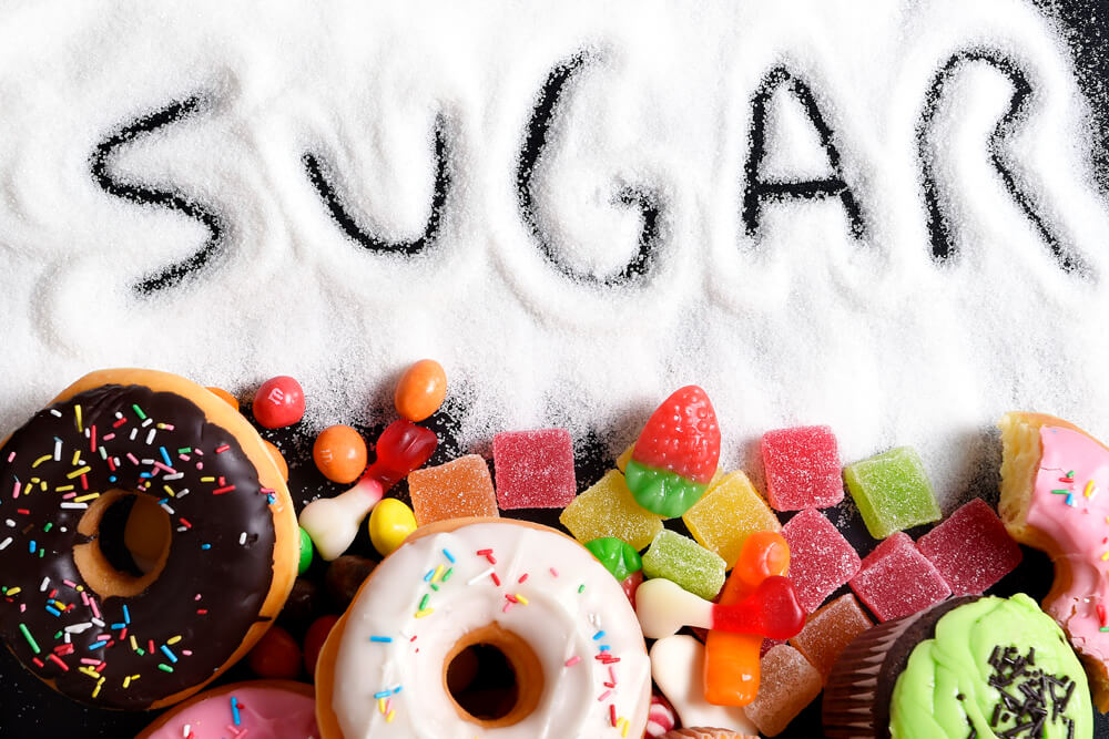 the word sugar written in sugar surrounded by donuts and candy