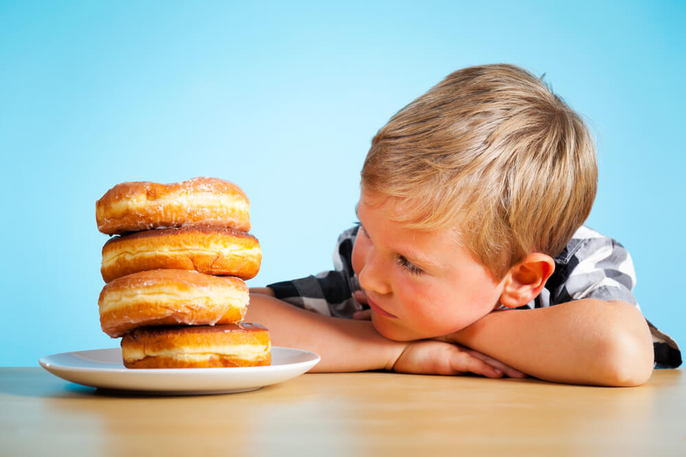 young blonde boy staring at a stack of glazed donutes