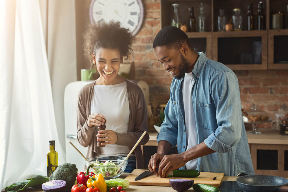 african american couple in kitchen with healthy food