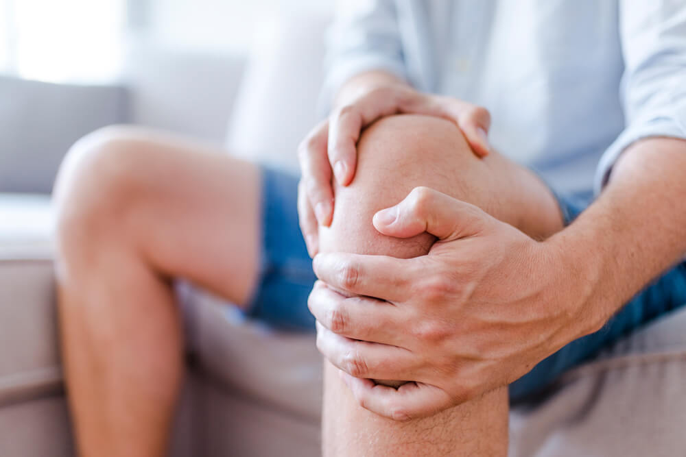 man holding his knee in pain sitting on a couch