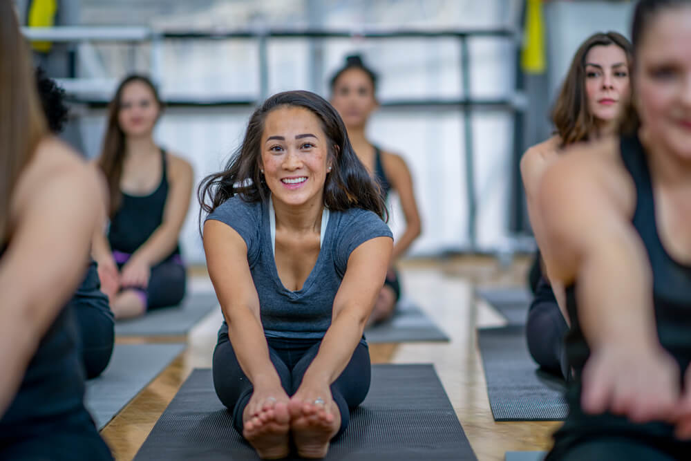 brunette woman sitting on a yoga matt stretching in a group class