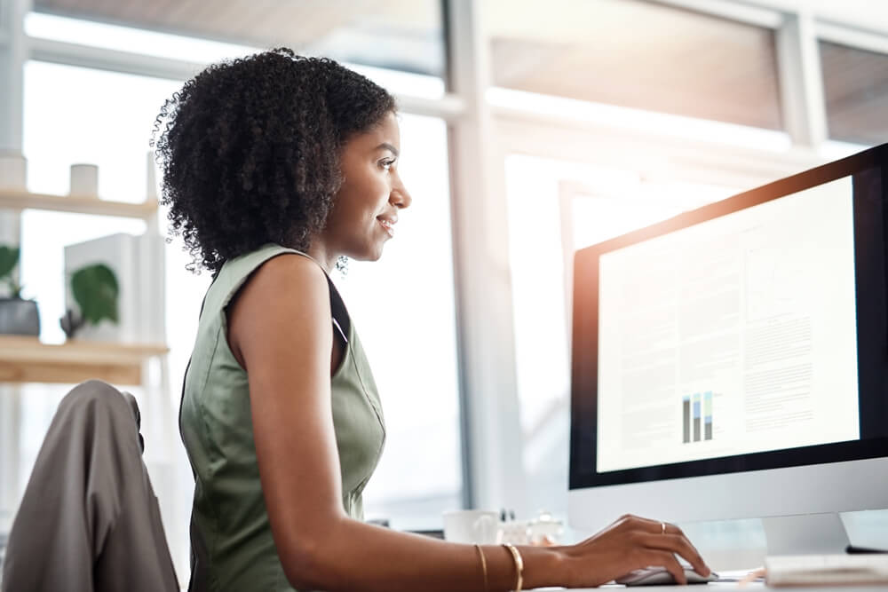 african american woman in a green dress sitting in an office looking at her computer monitor