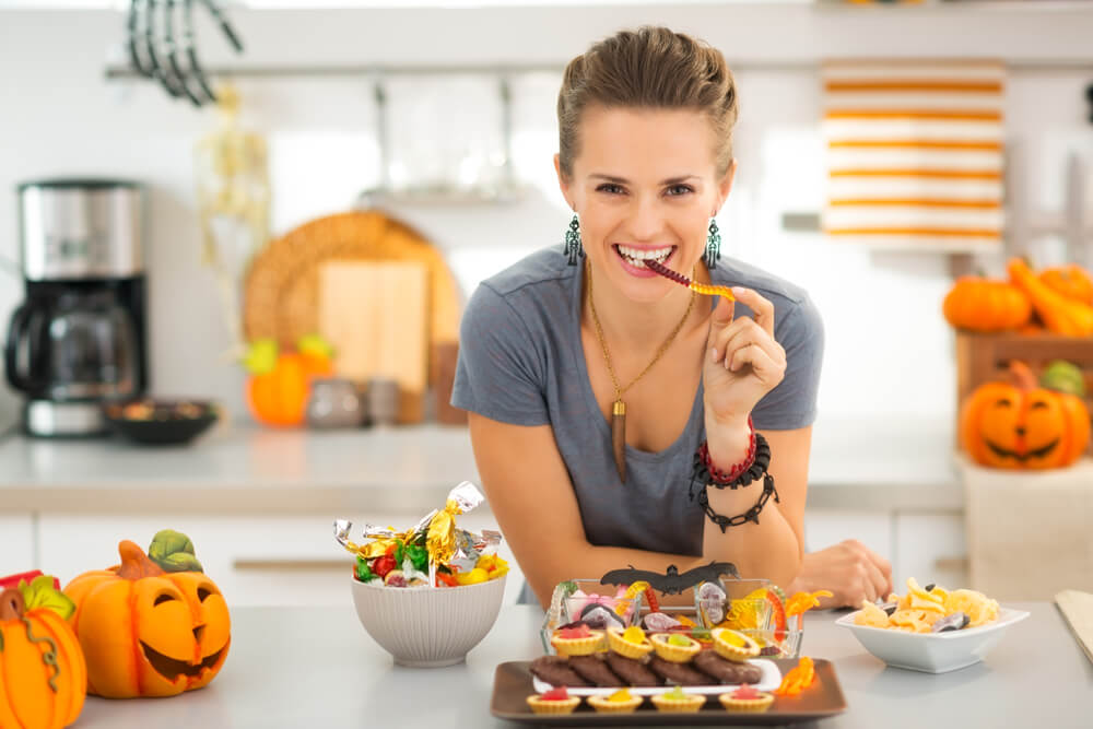 brunette woman eating halloween candy in the kitchen surrounded by more candy