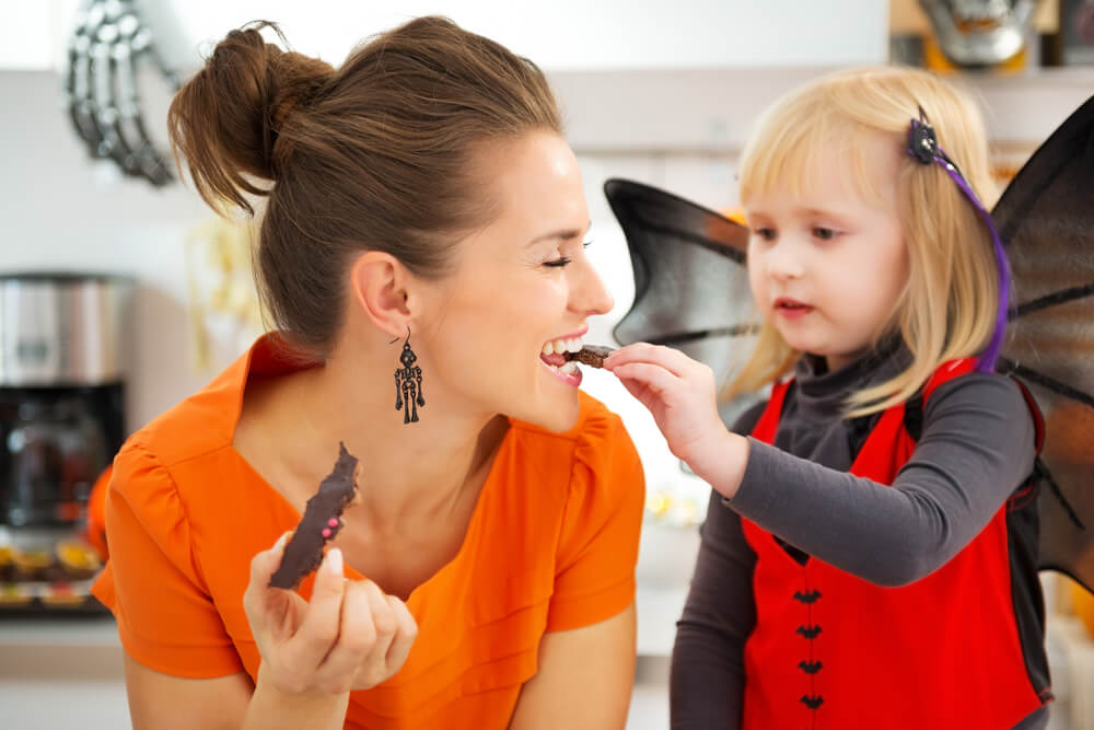 young daughter feeding her mom a piece of chocolate