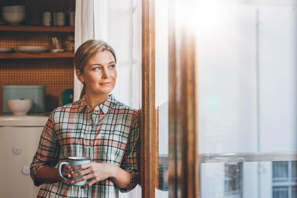 blond woman wearing plaid shirt holding mug reflecting her day