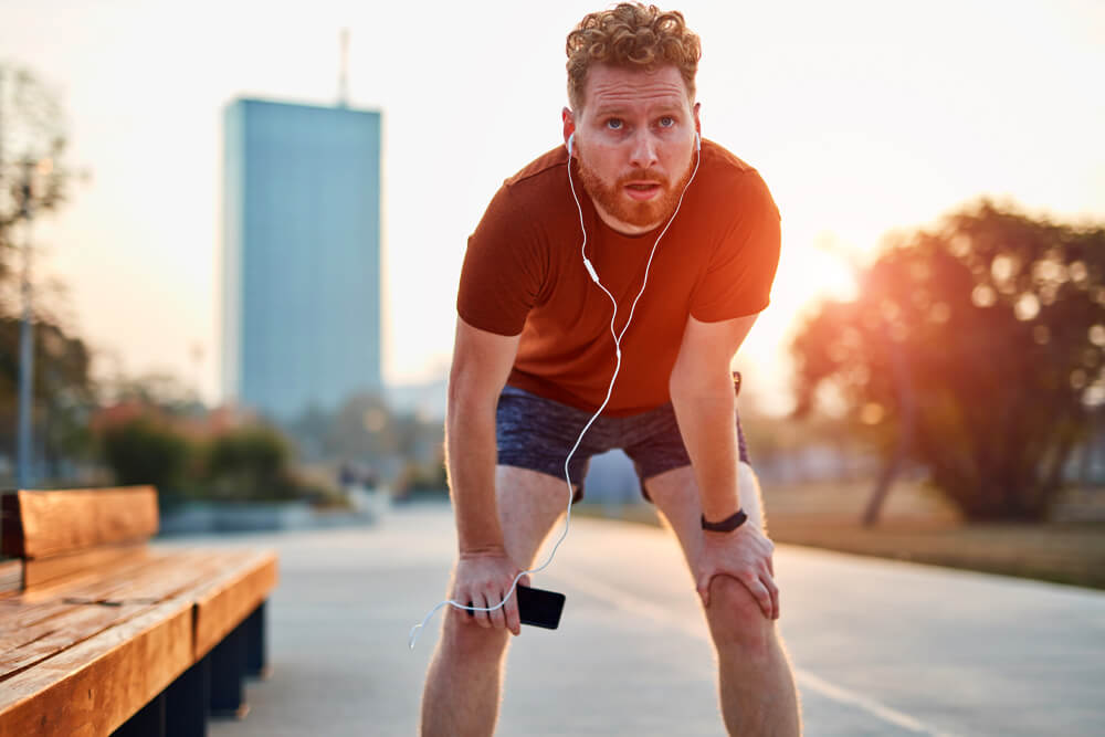 curly red haired man running in an urban park