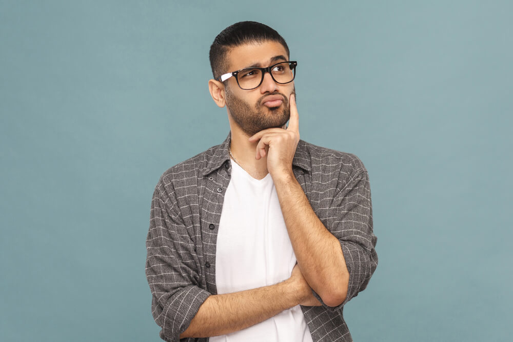 dark haired man wearing glasses in deep thought