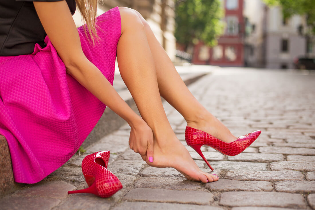 woman wearing red heels rubbing her ankle in pain