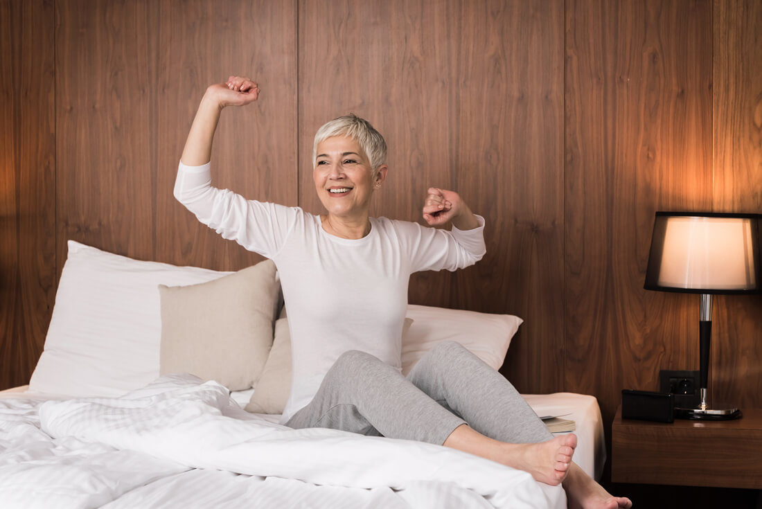 older woman waking up from bed
