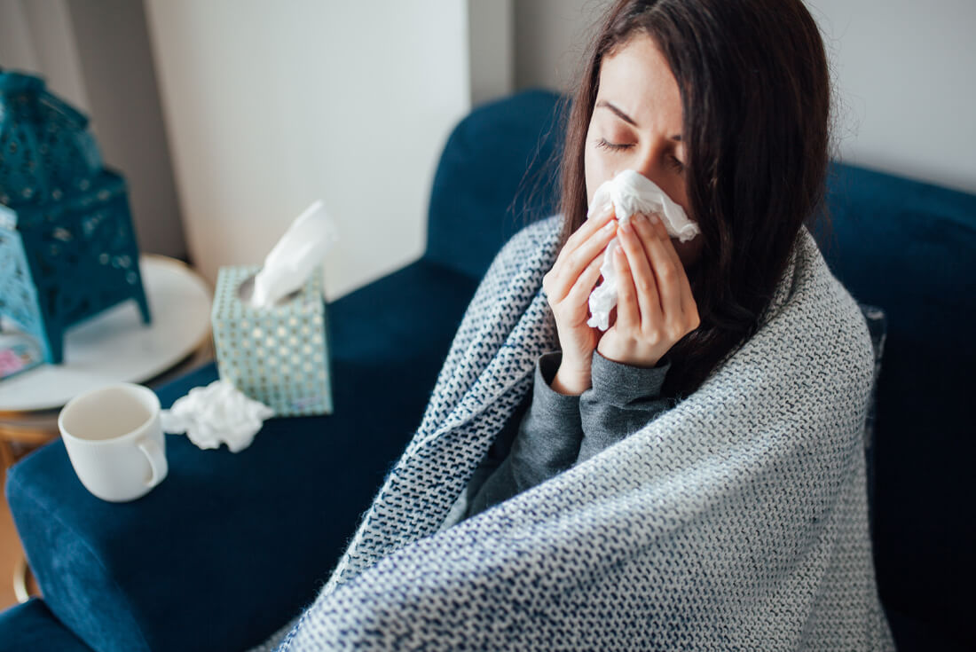 sick brunette woman sitting on blue couch wrapped in a kitted blanket with tissues